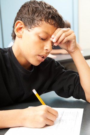 illiteracy: Handsome school boy struggling to finish a test in class.   Stock Photo