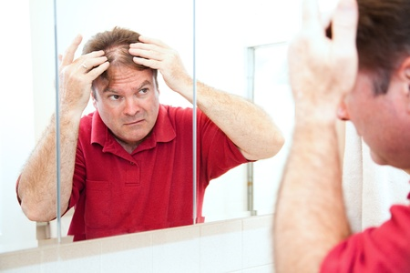 thinning: Middle aged man checking for thinning hair in the mirror.