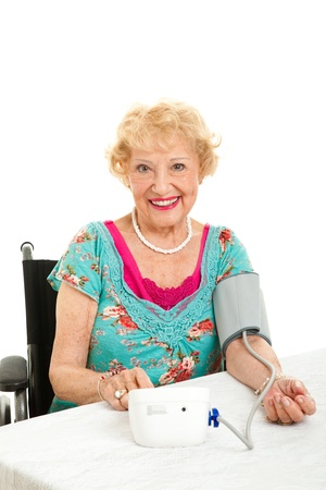 cuff: Senior woman taking he own blood pressure at home.  Isolated on white background.