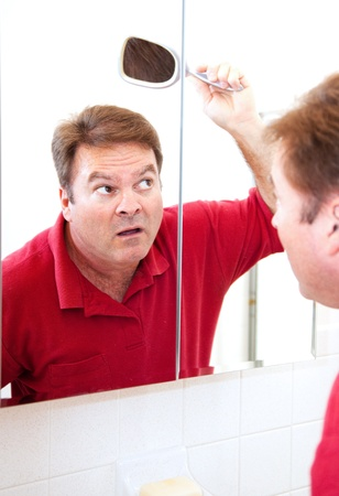 Mature man in his forties uses a mirror to check for bald patches in his hair.   photo