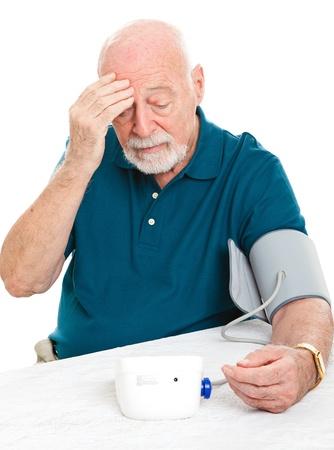 ipertensione: Preoccupato uomo anziano controlla la pressione sanguigna a casa.