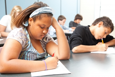 struggling: Classroom of diverse students taking objective testing in school.  Stock Photo