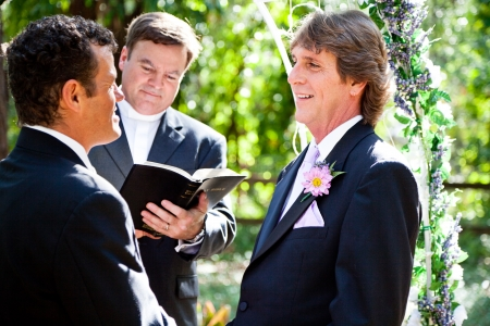 Handsome groom looks lovingly into his partners eyes during their wedding ceremony.   photo