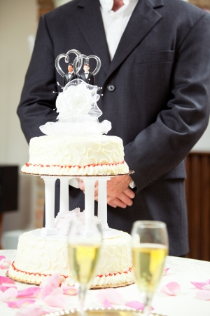 Closeup of wedding cake with champagne in the foreground and a groom in background.  Cake has two grooms Stock Photo - 15563464