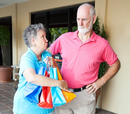 Senior woman addicted to shopping looks guilty as she explains to her husband.   Banco de Imagens