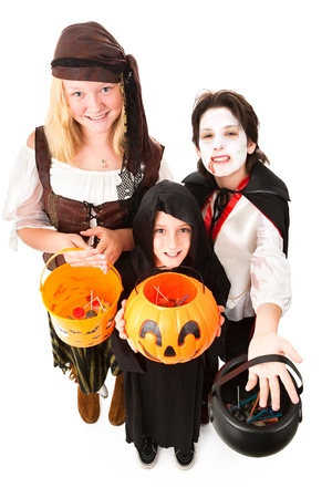 Three children in Halloween costumes, trick or treating.  Full body isolated on white.   photo