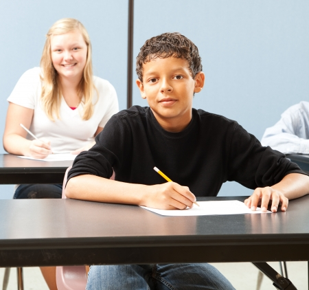 Handsome adolescent boy in school classroom, sitting at desk.