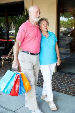 Happy senior couple walking at the mall with shopping bags.