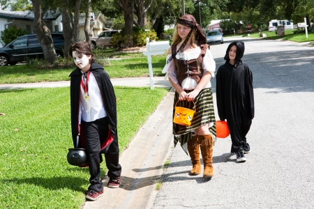 Children in Halloween costumes trick or treating in their neighborhood.  They look disappointed not to have gotten more candy.   photo
