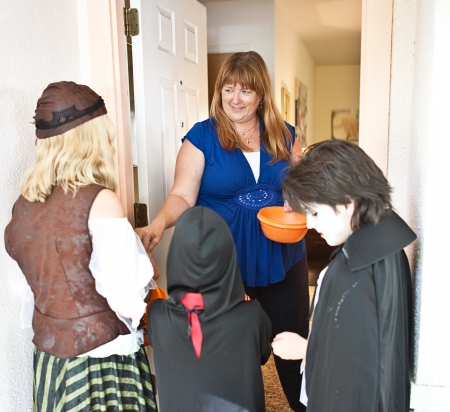 trick or treat: Nice woman passing out Halloween candy to trick or treaters at her door.