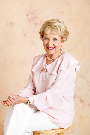 Portrait of beautiful, elegant senior woman sitting on a stool. photo