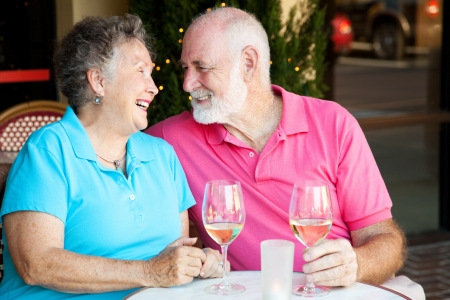 Senior couple flirting and laughing together over a glass of white wine.   photo