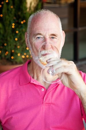 Senior man enjoying a glass of white wine.   photo