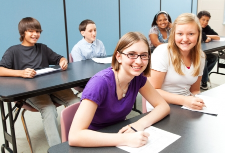 test glass: Six adolescent school children sitting at tables in class.   Stock Photo