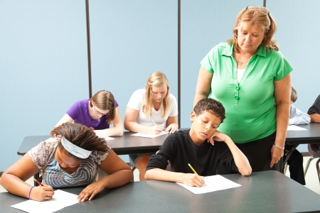 school exam: Teacher supervising students who are taking a standardized achievement test.
