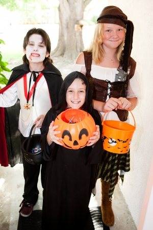 tricks: Three kids in Halloween costumes going trick or treating door-to-door.  Focus on little boy in front.   Stock Photo