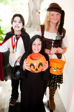 treats: Tre bambini in costumi di Halloween dolcetto o scherzetto andando porta a porta. Focus sul bambino di fronte.