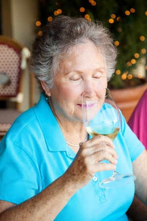 Senior woman enjoying the fragrance of a good glass of white wine.   photo