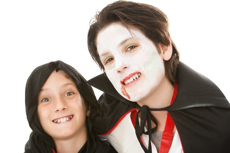 Two brothers dressed in their Halloween costumes.  One is a goblin and the other is a vampire.  White background.   photo