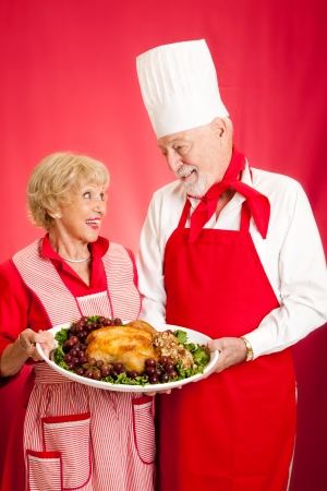 Chef and homemaker collaborated on making a delicious holiday turkey dinner.  Red background.   photo