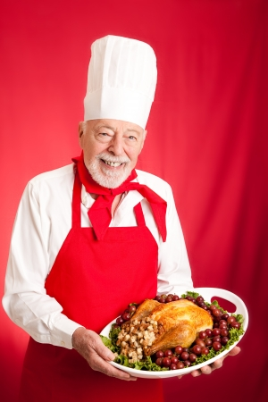 food industry: Chef holding a Thanksgiving or Christmas turkey stuffed on a platter.