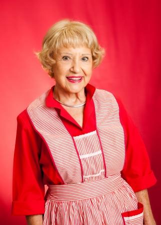 그녀의 빈티지 앞치마 달콤한 수석 아가씨. 완벽한 복고풍 할머니 나 주부. 빨간색 배경입니다.