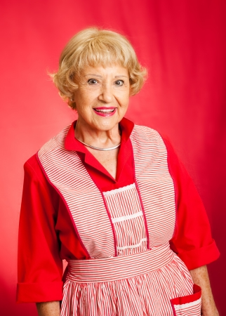 retro woman: Sweet senior lady in her vintage apron.  Perfect retro grandmother or homemaker.  Red background.   Stock Photo