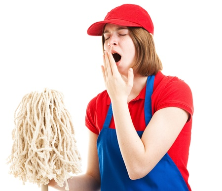 first job: Tired teenage girl in her work uniform, holding a mop and yawning.  Isolated on white.   Stock Photo