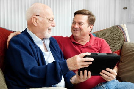 listening to people: Senior man using tablet PC with his adult son.