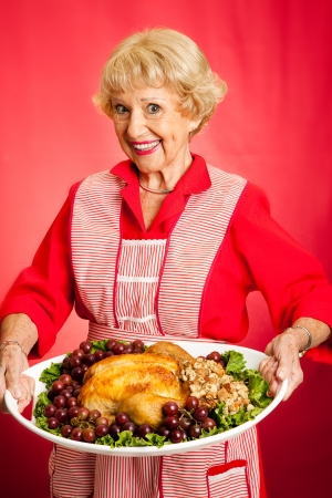 stuffing: Pretty grandmother serving holiday turkey dinner.  Red background.