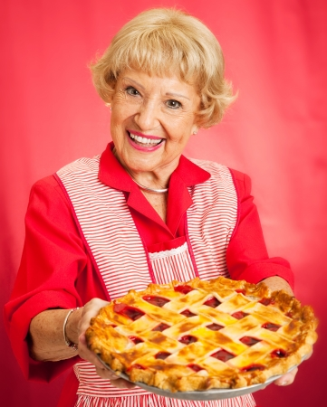 Sweet grandmother in vintage apron holding a delicious homemade cherry pie.