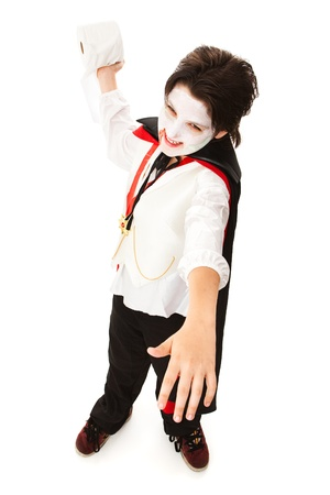 Little boy dressed as a vampire for Halloween, getting ready to throw a roll of toilet paper.   photo