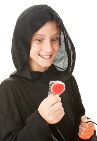 eagerness: Little boy dressed in his halloween costume, looking hungrily at a lollipop.  Isolated on white.   Stock Photo