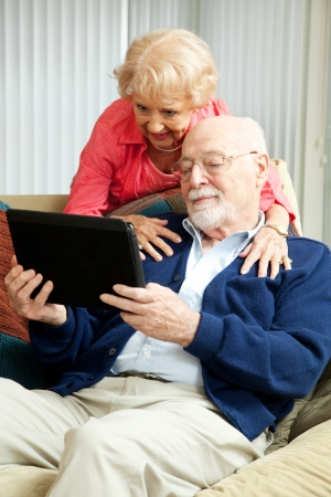 Senior couple relaxing at home, using their tablet PC.   photo