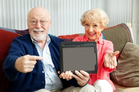 Senior couple pointing to a message on their tablet PC. Stock Photo - 15844254
