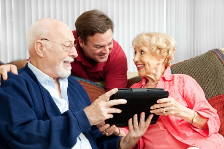 Senior couple get a gift of a tablet PC from their adult son. Stock Photo - 15844270