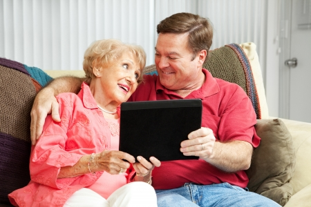 70s adult: Adult son teaching his elderly mother how to use her new tablet PC.