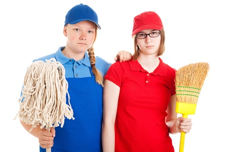 first job: Two serious looking teenage girls, dressed in uniforms for menial jobs and holding a broom and mop.  Isolated on white.