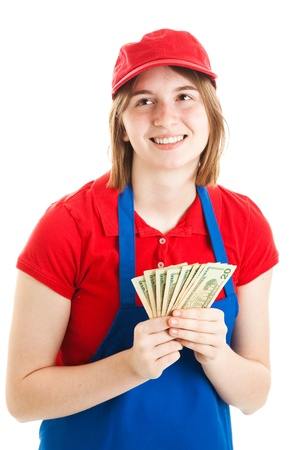 first job: Teenage girl in her work uniform, holding a handful of money.  Isolated on white.