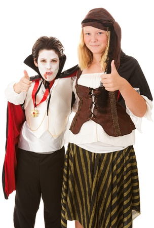 Brother and sister in their halloween costumes, giving thumbs up signs.  Isolated on white.