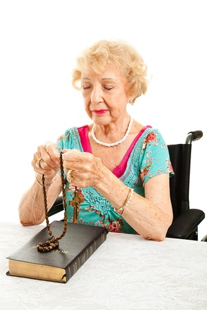 Elderly Catholic grandmother in wheelchair praying with rosary beads.  White background.   photo