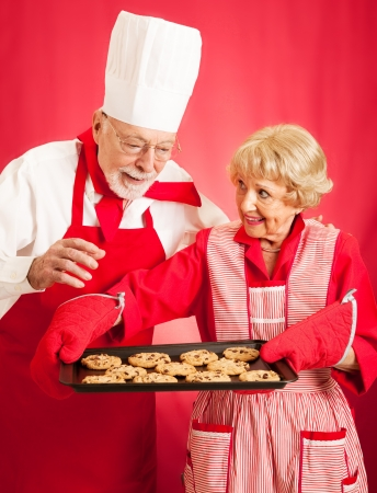admires: Chef admires the delicious chocolate chip cookies baked by a homemaker.   Stock Photo