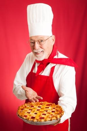 gorro cocinero: Chef sosteniendo un pastel de cereza fresco al horno sobre un fondo rojo.
