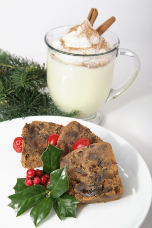 Delicious Christmas fruitcake and creamy eggnog with cinnamon and nutmeg. Stock Photo - 16246657
