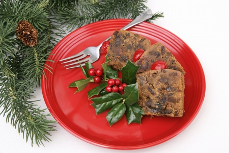 Delicious Christmas fruitcake on a red plate, with pine branches and holly garnish.   Stock Photo - 16246662