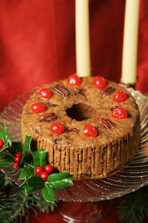 Christmas fruitcake on a glass plate, with candlesticks and holly on a red background.   Stock Photo - 16246673