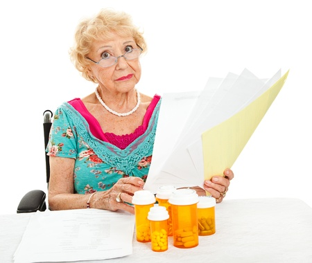 medical expenses: Disabled senior woman, unhappy about mounting medical expenses.  White background. Stock Photo