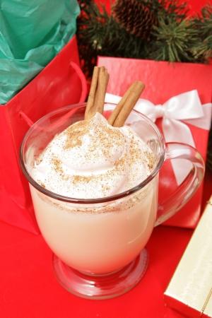 eggnog: Delicioso ponche de huevo cremoso en rojo con los regalos de Navidad.
