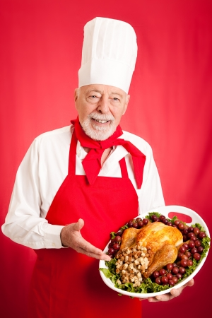 Handsome, experienced chef holding stuffed turkey dinner.  Red background.   photo