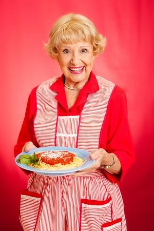 mere cuisine: Douce grand-m�re r�tro tenant une assiette de spaghetti frais, chaudes italiennes avec sauce marinara. Fond rouge. Banque d'images